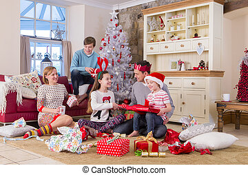 Family opening presents at Christmas Time - Two Generation...