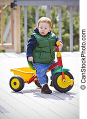 Boy on bike - Young boy sitting on toy bike outside
