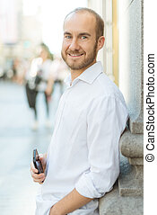 Smiling man with phone - Happy man leaning on a wall in the...