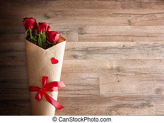 red roses on wooden background the concept of love and...
