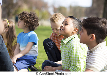 Lesson Outdoors - Small group of children sitting on the...