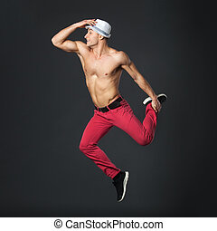 Young happy male dancer jumping in studio - Young happy male...
