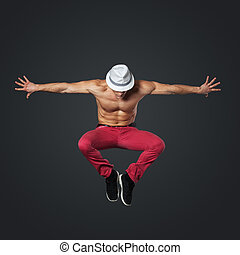 Young male dancer jumping in studio - Young male dancer...