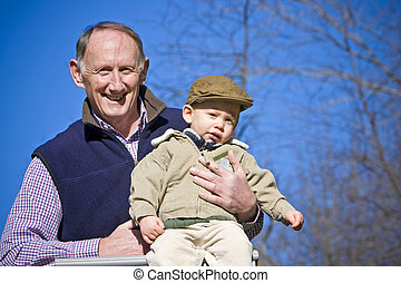 Happy grandfather holding cute grandson outside