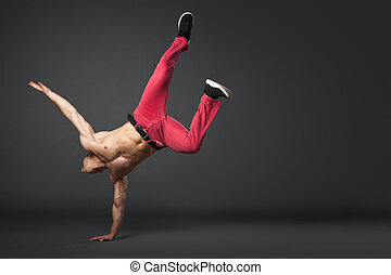 Young male professional dancer B-boying on gray background -...