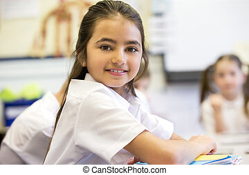 Happy at School - School girl smiles at the camera as she...