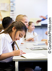 Working At School - Schoolgirl sits at her desk while...