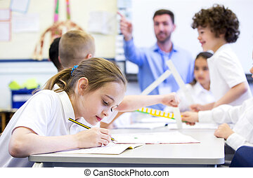 Working at School - Schoolgirl sitting at a desk with other...