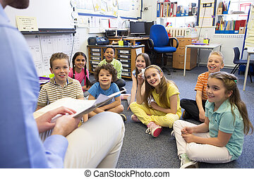 Story Time in a Classroom - A group of children sit on the...