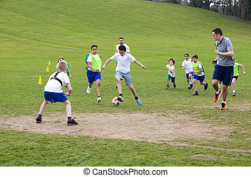 Get The Ball. - Adults on grassed area with school children...