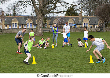 Soccer Practice - Adults on grassed area with school...