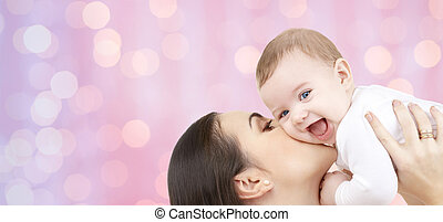 happy mother kissing her baby over pink lights - family,...