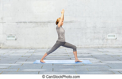 woman making yoga warrior pose on mat outdoors - fitness,...