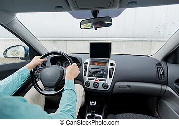 close up of young man with tablet pc driving car -...