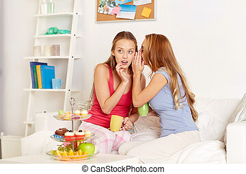 young women drinking tea and gossiping at home - friendship,...