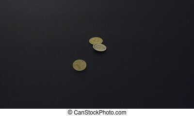 Falling coins on black background.