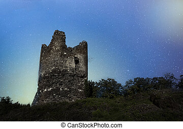 Old castle tower on a night sky background