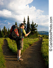 Checking GPS at a trail fork - A hiker checks his GPS unit...