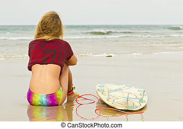 Keen surfer - Keen female surfer sitting on the sand looking...
