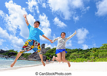 Father and daughter jumping on beach at Thailand