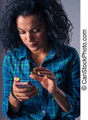 Woman texting on her cell phone - Sullen mixed race woman...