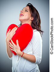 Young woman in love clutching a red heart with a smile of...