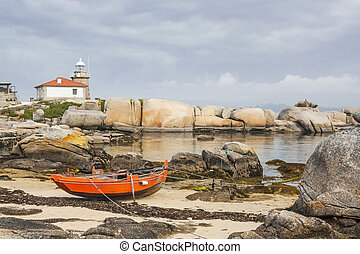 Red boat and lighthouse on rocky coast - Red boat and...