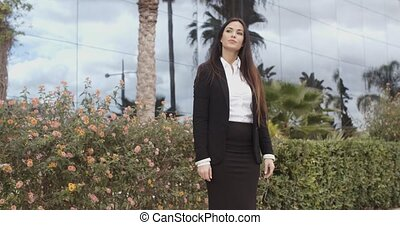 Stylish businesswoman standing outside her office in a...