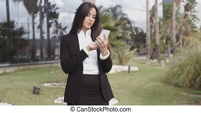 Smiling businesswoman checking her mobile phone - Smiling...