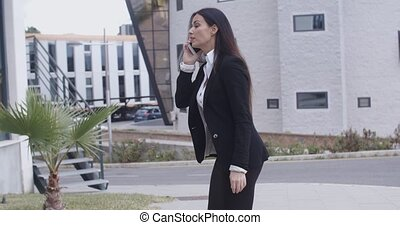 Businesswoman walking through an office complex - Stylish...
