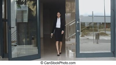 Young businesswoman exiting a modern office
