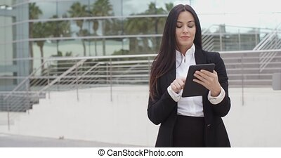 Stylish businesswoman using her tablet computer as she...