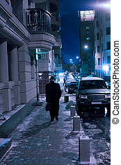 old man goes on winter night street in downtown