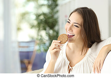 Happy girl eating a dietetic cookie sitting on a couch at...