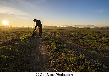 Man standing on a country road leaning down to pet his black dog in a beautiful landscape