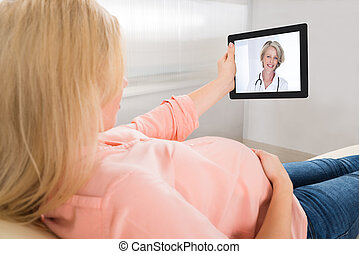 Pregnant Woman Video Conferencing With Doctor On Tablet...