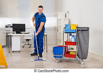 Janitor Mopping Floor In Office - Full length of male...