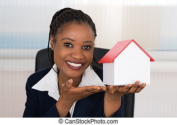 Businesswoman Presenting A House Model - Smiling Young...
