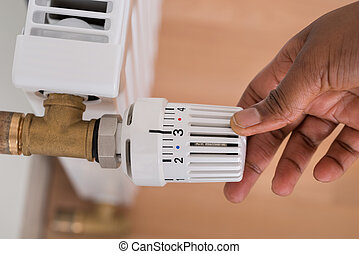 Persons Hand Adjusting Radiator Temperature - Close-up Of...