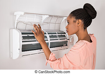 Woman Opening Air Conditioner - Young African Woman Opening...