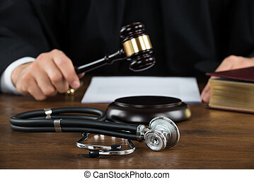 Judge Striking Mallet With Stethoscope At Desk - Midsection...
