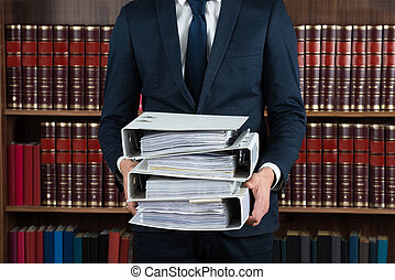 Lawyer Carrying Stack Of Ring Binders - Midsection of male...