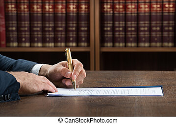 Lawyer Writing On Legal Documents At Desk - Cropped image of...
