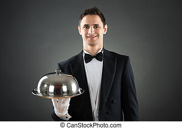 Happy Waiter Holding Tray With Cloche