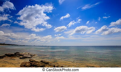 Stones in Transparent Shallow Azure Sea Blue Sky White Clouds