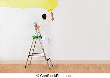 Man Painting Wall With Yellow Paint Roller - Rear view of...