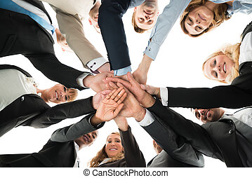 Confident Business Team Stacking Hands While Standing In...