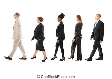 Side View Of Business Team Walking In Row - Full length side...