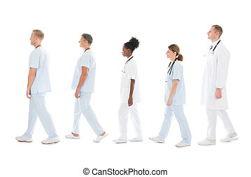 Side View Of Medical Team Walking In Row - Full length side...