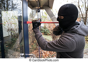 Man Using Crowbar To Open Glass Door - Hooded man using...